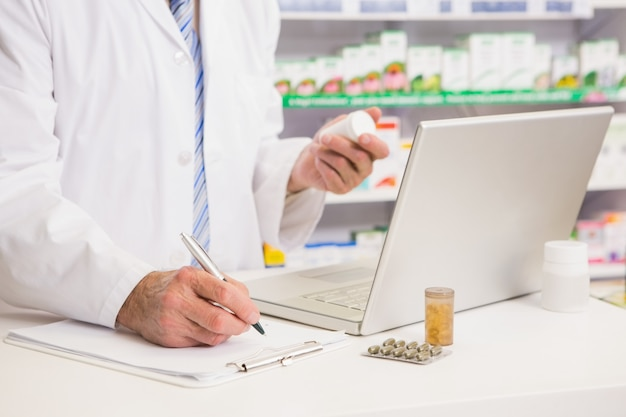 Pharmacist writing on clipboard and holding medication