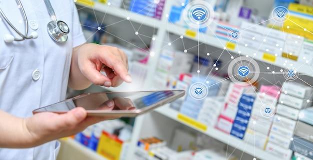Pharmacistholding computer tablet using for filling prescription in pharmacy drugstore