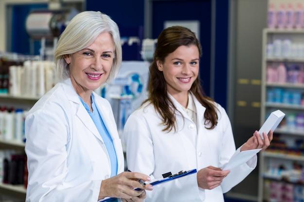 Фармацевты проверяют и выписывают рецепт на лекарства в аптеке