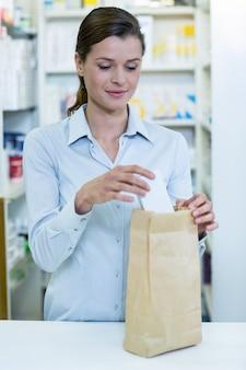 Фармацевты упаковывают лекарства в бумажный пакет