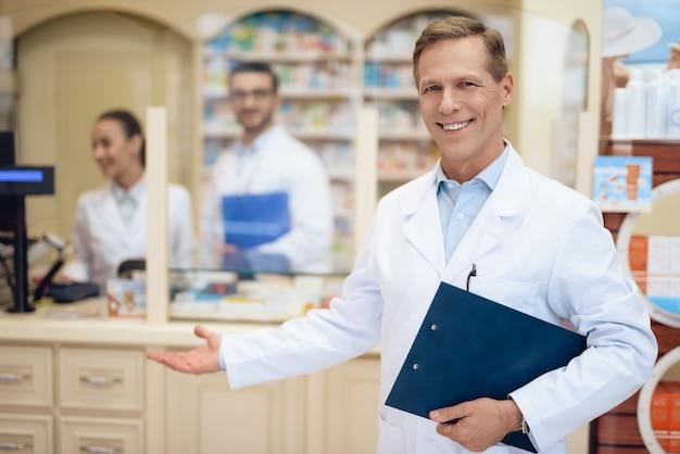 薬剤師は薬局に立って、書類の入ったフォルダーを持っています。