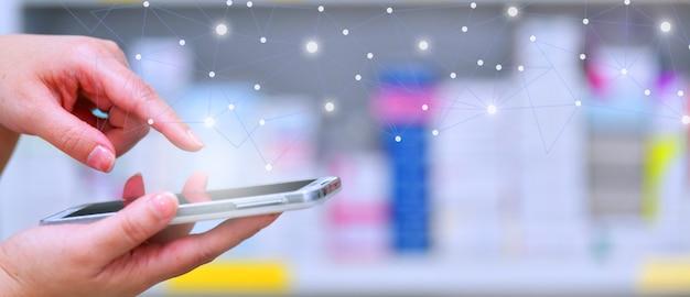 Pharmacistusing mobile smart phone for search bar on display in pharmacy drugstore