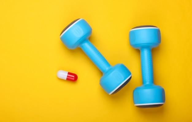 스포츠 약리학. 아령과 노란색 배경에 캡슐입니다. 비타민, 스테로이드. 평면도