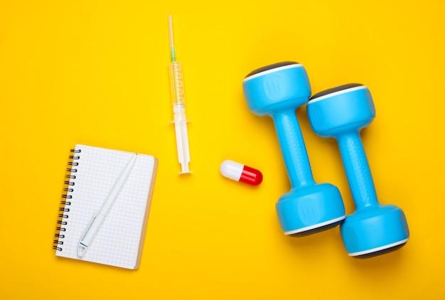 스포츠 약리학. 아령, 캡슐, 주사기, 노란색 배경에 노트북. 비타민, 스테로이드. 평면도