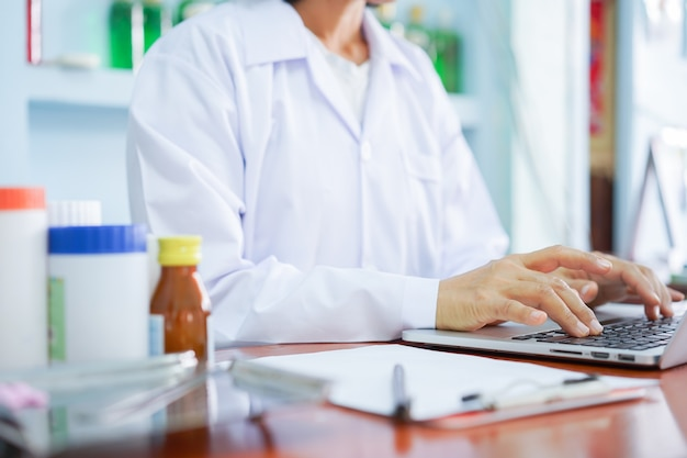 Pharmacy doctor trying to search feature of medicine on laptop