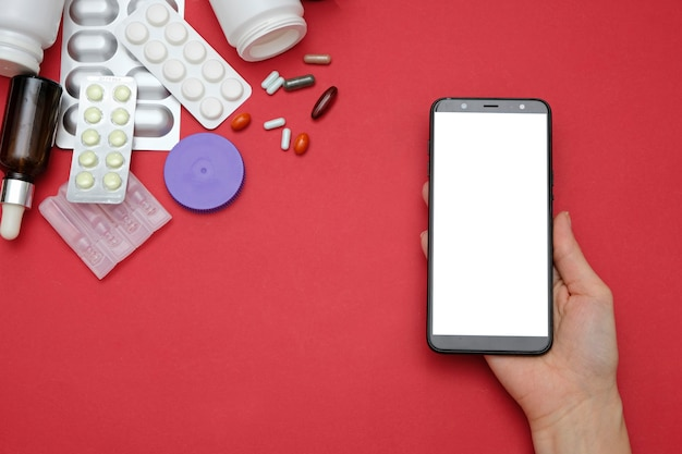 Pharmacy and drugstore online concept. medicine pills and smartphone in hands on red background
