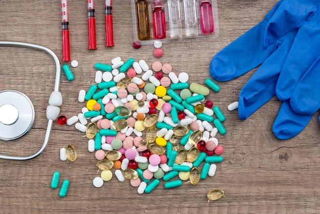 製薬業界の構想。木製のテーブルの上の丸薬とアンプル