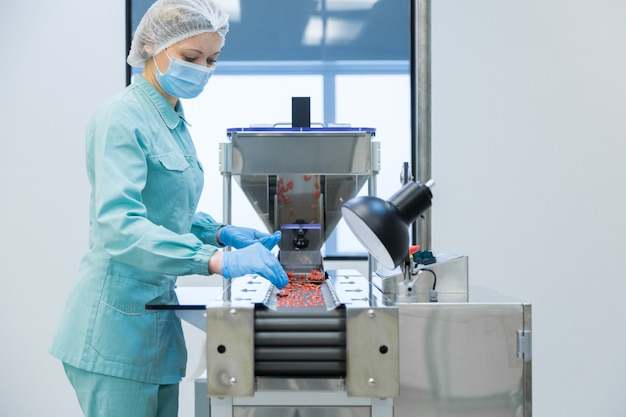 Pharmacy industry woman worker in protective clothing operating production of tablets