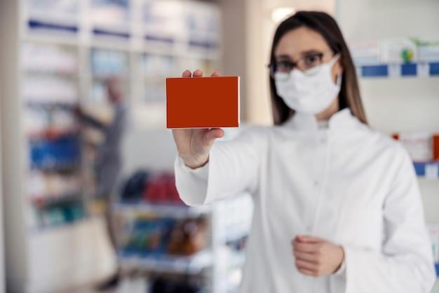 레드 보드로 제품을 포장하기위한 약국 모형. 여자의 손은 의약품 상자를 들고, 초점은 상자에 있고 여자의 초상화는 광고를위한 공간 복사