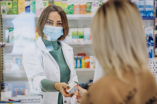 Pharmasict serving customer at drug store