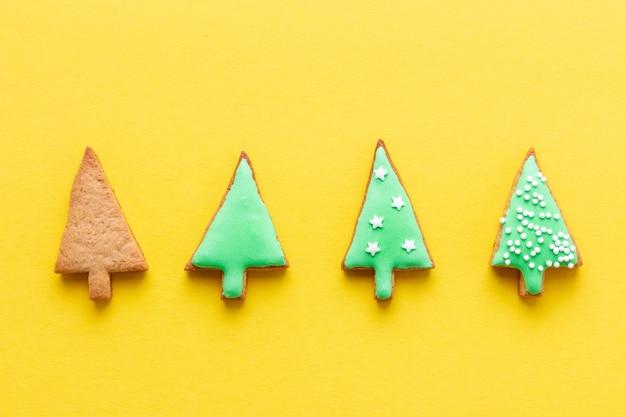Этапы украшения рождественских пряников в виде елок на желтом