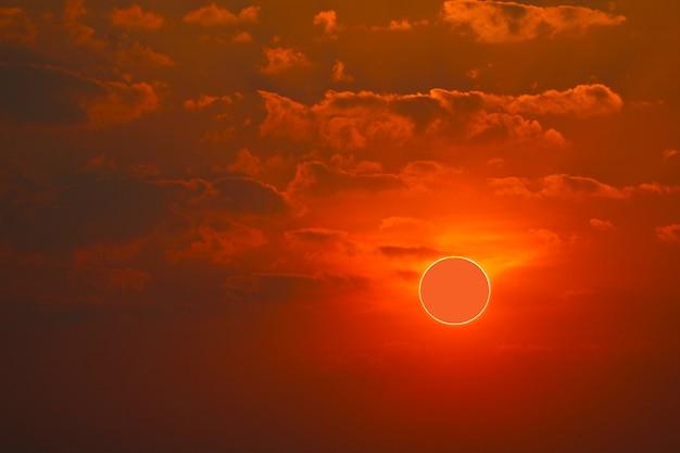 Phenomenon of partial sun eclipse over sea and sunset sky
