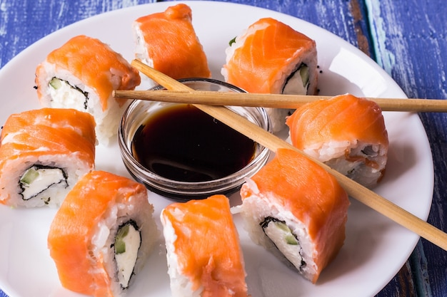 Philadelphia maki sushi made of fresh raw salmon, cream cheese and cucumber with soy sauce
