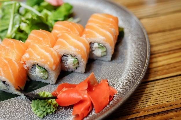 Филадельфия маки суши из сливочного сыра филадельфия внутри, свежий сырой лосось снаружи. подается с соусом