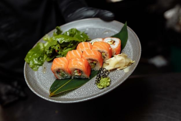 Philadelphia maki sushi из сливочного сыра филадельфия внутри, свежего сырого лосося снаружи. с соусом.