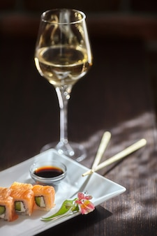 Суши-роллы филадельфия маки с лососем, сырным кремом, огурцом на белой тарелке и бокалом вина