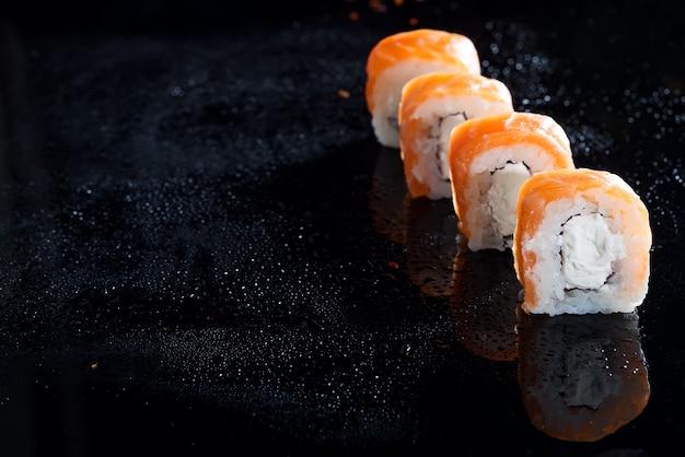Philadelphia roll classic on black glass background. japanese sushi food.