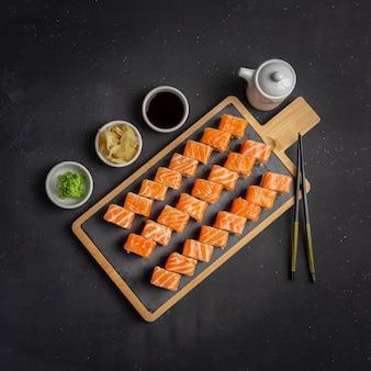 Philadelphia roll classic dark stone on the board. salmon, philadelphia cheese, cucumber, avocado. japanese sushi. top view, copy space