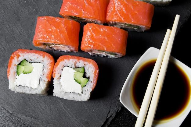 Ролл филадельфия суши с лососем на темном фоне. вид сверху