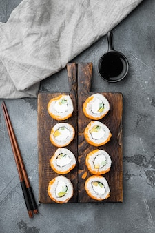 Ролл филадельфия суши с лососем, креветками, авокадо, сливочным сыром, на сером каменном фоне, плоская планировка, вид сверху