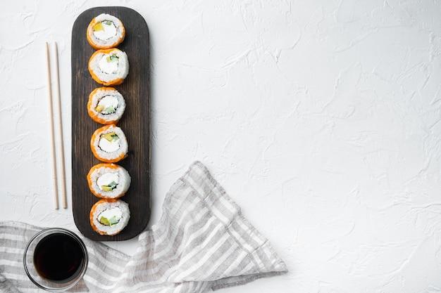 Ролл филадельфия суши с лососем, креветками, авокадо, сливочным сыром, на белом камне