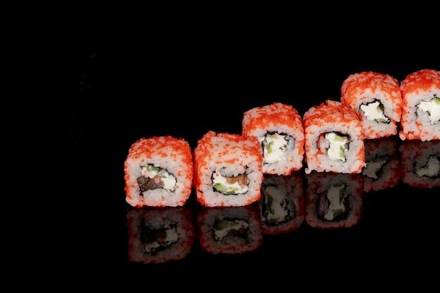 フィラデルフィアロールは、反射のある黒い背景にサーモン、チーズ、キュウリを添えています。寿司フィラデルフィア。
