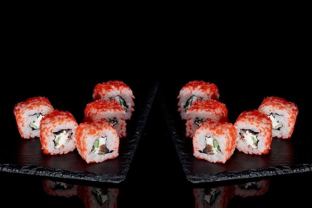 Ролл филадельфия с лососем, сыром и огурцом на черном фоне с отражением. суши филадельфия.
