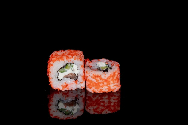 Philadelphia roll with salmon, cheese and cucumber on a black background with reflection. sushi philadelphia