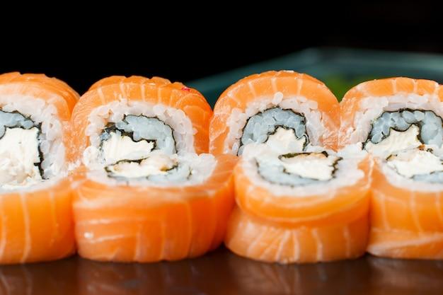 필라델피아는 연어, 크림 치즈, 오이, 아보카도, 노리 클로즈업으로 롤링합니다. 일본 전통 요리.