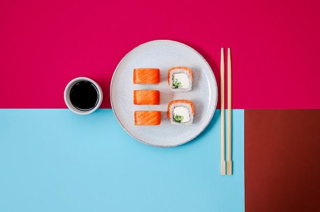 Роллы филадельфия с лососем, рыбой, огурцом и сыром на тарелке с соевым соусом на красочном фоне минимальная концепция