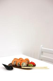 필라델피아는 젓가락 옆에있는 흰색 테이블에 스시 바에서 연어와 함께 롤백합니다. 스시 메뉴. 일본 음식 개념. 텍스트를 놓습니다. 수직 방향