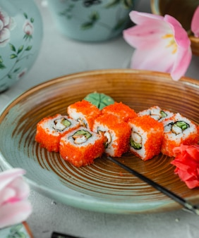 Philadelphia rolls with wasabi and ginger inside decorative plate.