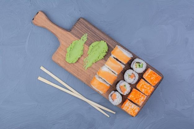 Involtini di maki philadelphia, salmone e sake con wasabi su un piatto di legno.