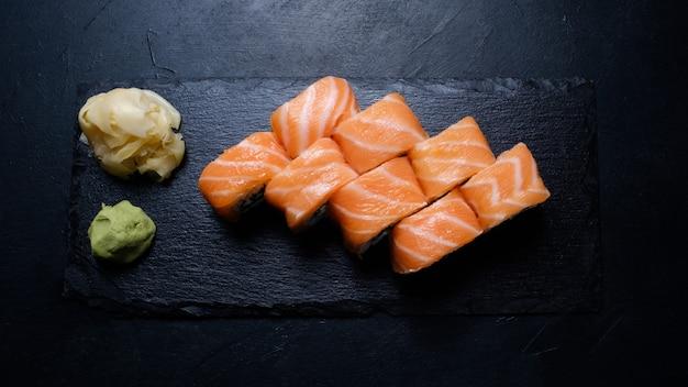 フィラデルフィアサーモン寿司は、暗い背景にわさびと生姜を添えて巻かれています。フードフォトグラフィーアート。