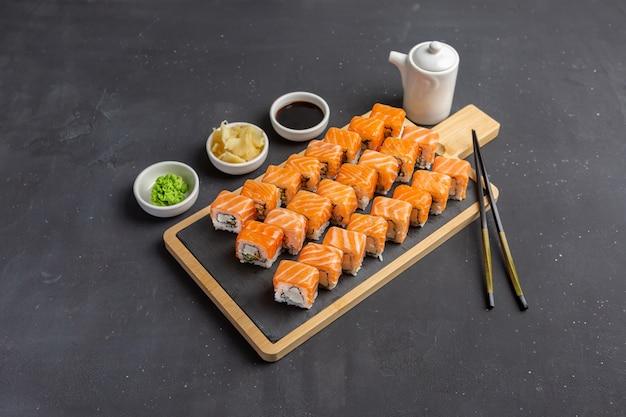 Philadelphia sushi roll made of fresh salmon, avocado and cream cheese inside. traditional japanese cuisine