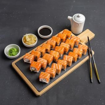 Суши-ролл «филадельфия» из свежего лосося, авокадо и сливочного сыра внутри. традиционная японская кухня