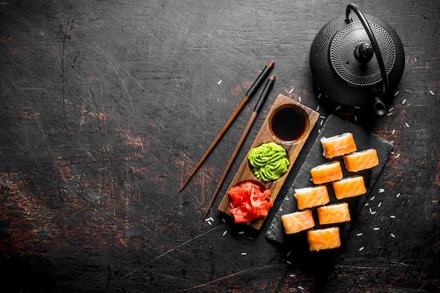 Суши-ролл филадельфия на каменной подставке с имбирем, васаби и соевым соусом на черном деревенском столе