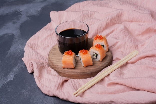 Philadelphia sushi roll, soy sauce and chopsticks on pink tablecloth.