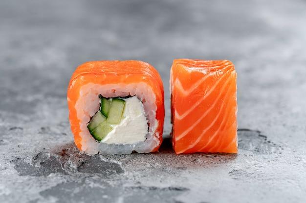 灰色の石の背景にサーモン、チーズ、キュウリのフィラデルフィア巻き寿司。日本のメニューのコンセプト。