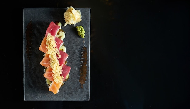 Philadelphia sushi roll with salmon and tuna crab, avocado, served on a dark plate with wasabi and ginger. isolation on a black table. japanese food