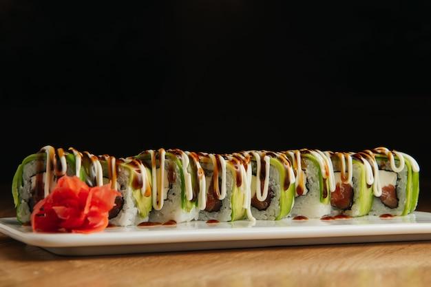 Суши-ролл филадельфия с соусом терияки на белой тарелке