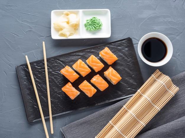 灰色の背景に黒い織り目加工のプレートスタンドでフィラデルフィア寿司ロール。上面図、フラットレイ。日本料理