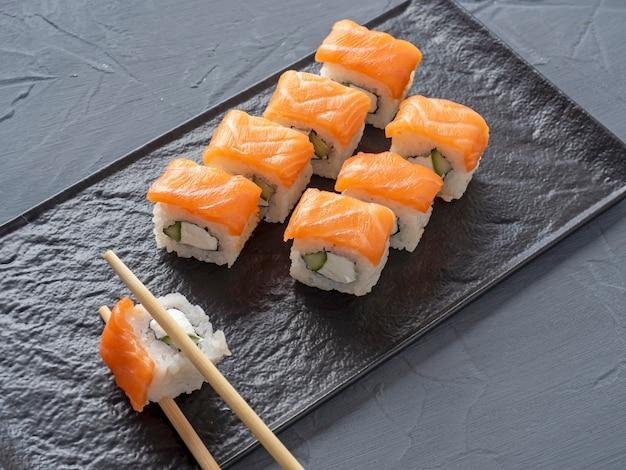 フィラデルフィアの寿司は、灰色のテーブルの上にある黒い織り目加工のプレートスタンドに巻かれています。 1本のロールは竹の棒で取られます。側面図、日本食