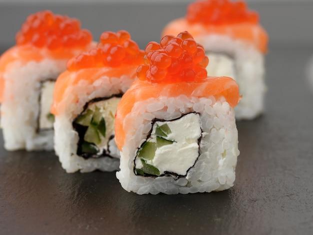 Филадельфия суши с красной икрой на черной грифельной доске, крупным планом