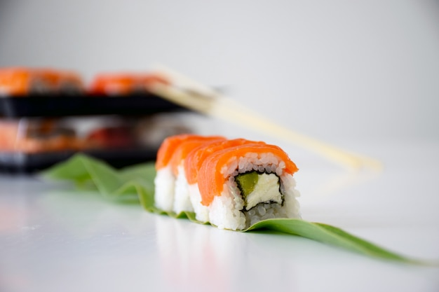 Philadelphia sushi with salmon, avocado and cheese on green leaf