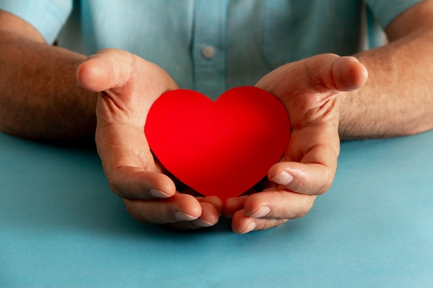 慈善活動と慈善の概念。紙のハートを提供する手。セレクティブフォーカス。