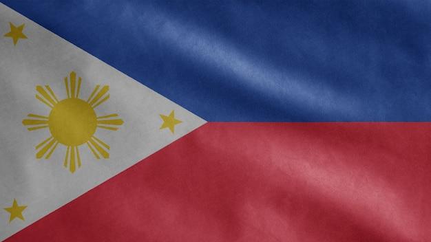風に揺れるフィリピンの旗。滑らかなシルクを吹くフィリピンのバナーのクローズアップ