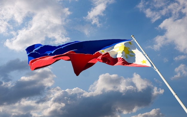 Philippine national flag waving in the wind against blue cloudy sky background low angle close-up