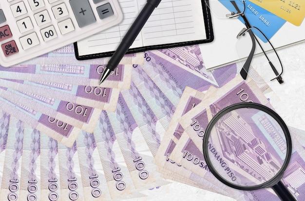 フィリピンペソの請求書とメガネとペンで計算機