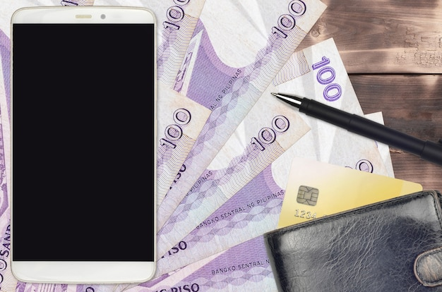 フィリピンペソの請求書と財布とクレジットカード付きのスマートフォン